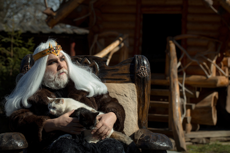 log house: Druid old man with long grey hair beard with crown in fur coat holds two cats and sits in wooden chair on log house background