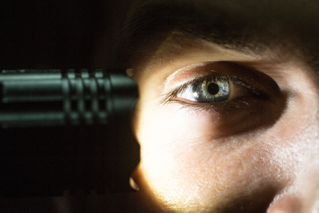 torchlight: young male with hairy eyebrow on serious face lighting on eye with flashlight in studio, closeup Stock Photo