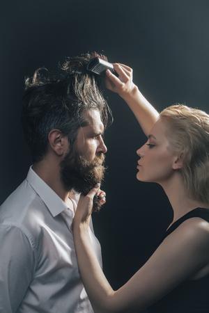 giovane coppia di bionda piuttosto parrucchiere pettinatura con i capelli pennello maschio bruna di uomo bello con la barba lunga barba in camicia bianca su sfondo grigio