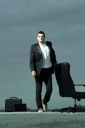 arm chair: handsome tired male businessman in black formal jacket and white shirt with laptop and leather arm chair outdoor with briefcase on cloudy sky background Stock Photo