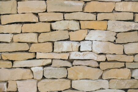 lithic: Old brick wall of beige uneven cracked stone surface on mason background