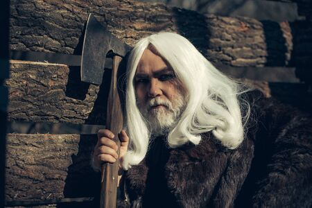 silver hair: Old man druid with long silver hair and beard in fur coat holding big sharp axe on wooden house background sunny day outdoor
