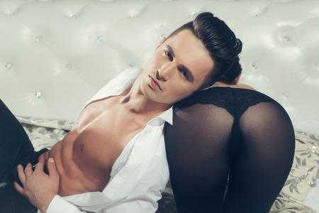 nackte brust: gut aussehender junger Mann mit sexy muskul�sen K�rper und nackte Brust mit Torso in offenen wei�en Hemd in der N�he von weiblichen Ges�� in schwarzen Str�mpfen