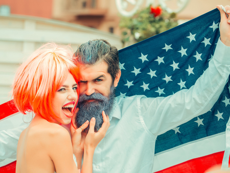 Happy young patriotic American couple with bright make up and hair celebrating Independence Day on 4th of July. American flag on the background, girl with the bright orange hair