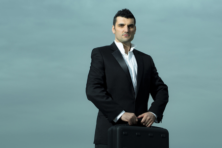 arm chair: handsome male businessman with serious face in black formal jacket and white shirt with brief case on leather office arm chair outdoor on cloudy sky background Stock Photo