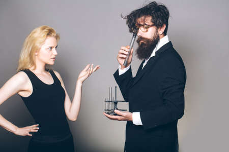 medical man: young couple of blond woman and handsome beaded man with long beard and hairstyle in glasses holding medical test tubes for chemical research on grey background Stock Photo