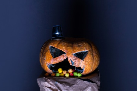 dragee: orange halloween pumpkin with scary face and silver pail as hat with colorful dragee candies in mouth on paper on grey background