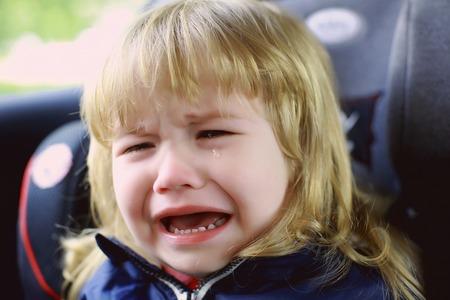 niños rubios: niño pequeño niño con las emociones faciales en la cara llorando infeliz y largo cabello rubio sentado en el coche con la lágrima en la mejilla, primer