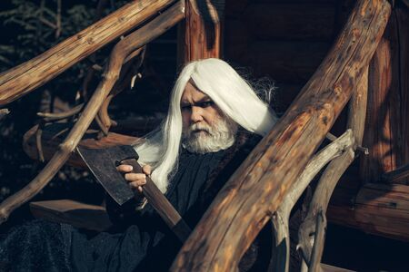 house coat: Old man druid with long silver hair and beard in fur coat holding big sharp axe on wooden house background sunny day outdoor