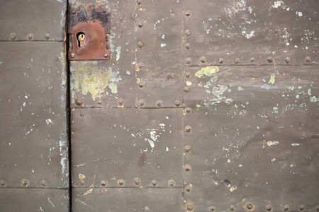 metallized: Metal door with mortise lock on rusty surface with old paint stains on metallized background Stock Photo