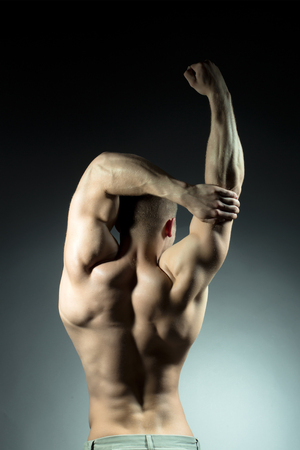 man power: Sexy muscular male back of athlete bodybuilder posing in power with raised hands and bare torso on grey background