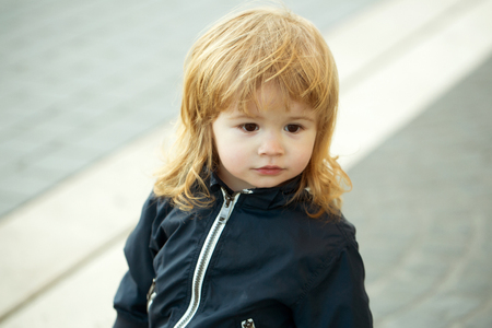 brown eyes: Little boy with pretty cute face brown eyes and blond curly long hair stands outdoor Stock Photo