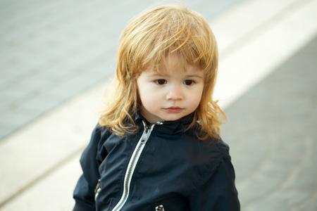 ojos marrones: Ni�o peque�o con la cara bastante mono ojos marrones y el pelo largo rizado rubio se encuentra al aire libre Foto de archivo