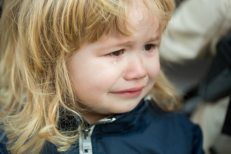 cries: Little boy with cute emotional face and blond long hair cries with tears outdoor