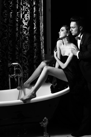 sexy bath: young handsome man in suit and bow with pretty sexy woman in elegant evening dress with skirt and long curly hair sitting in bath, black and white Stock Photo