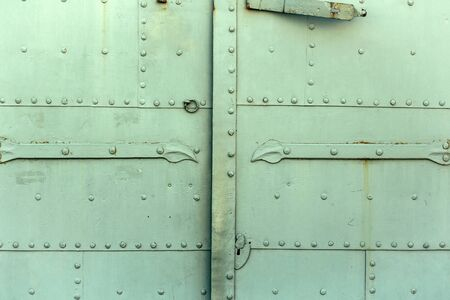 metallized: Old iron door fragment reinforced with rivets on green metallized background Stock Photo