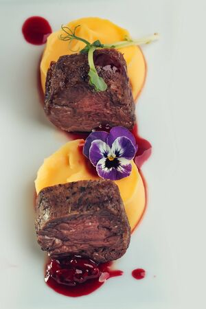 garnished: Beef fillet mignon grilled and garnished meat with colorful vegetables red berry sauce decorated with flower on white background