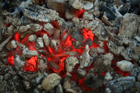 embers: open fire with hot ash and charcoal burning with bright orange flame as abstract background Stock Photo