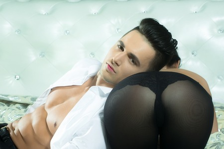 handsome young man with sexy muscular body and bare chest with torso in open white shirt near female buttocks in black stockings