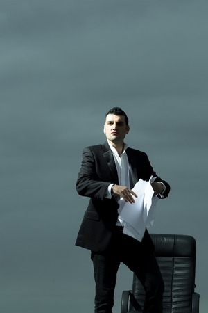 arm chair: handsome tired male businessman in black formal jacket and white shirt with paper near leather arm chair outdoor on cloudy sky background