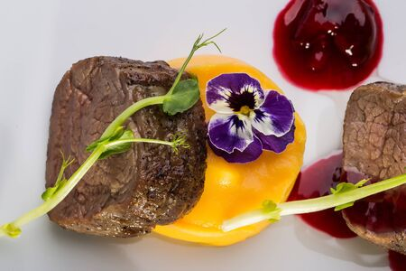 beefsteaks: Beef fillet mignon grilled and garnished meat with colorful vegetables red berry sauce decorated with flower on white background