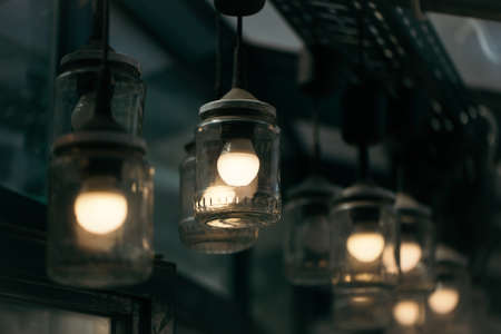 interior lighting: Original ceiling lamps of glass jars and bulbs lighting interior decor on grey blurred background