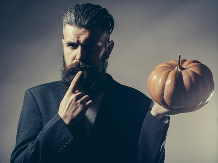 Handsome young man with long beard and moustache in black jacket holding halloween pumpkin in studio on grey background