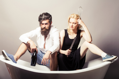 young family couple in quarrel of blonde pretty girl with kitchen utensils and bearded man with long beard holding wine bottle sitting on bathtub. household, everyday life and routine