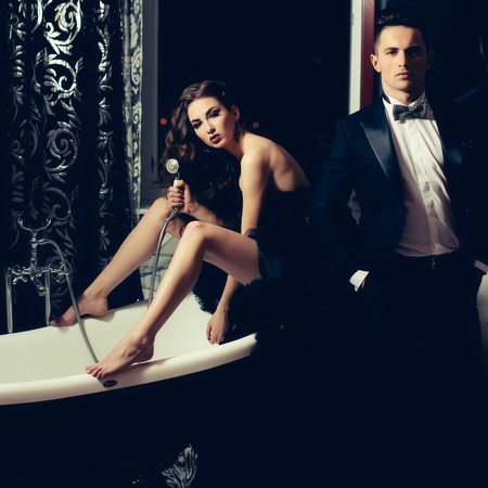 sexy bath: young handsome man in black suit and bow with pretty sexy woman in elegant evening dress with skirt and long curly hair sitting in bath Stock Photo