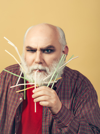 county somerset: Old bearded man with many drinking straws in long grey beard on serious face in red checkered shirt on yellow background