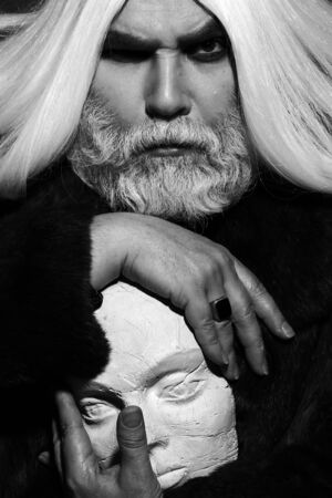 county somerset: old druid bearded man with long beard on serious face and hair in fur coat holding sculpture head in hands with ring, black and white