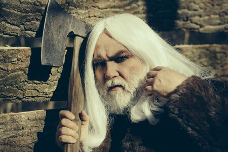 druid: Old man druid with long silver hair and beard in fur coat holding big sharp axe on wooden house background sunny day outdoor