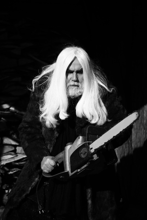 silver hair: Old man druid with long silver hair and beard in fur coat holding big chainsaw sunny day outdoor, black and white Stock Photo