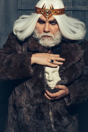 druid: old druid bearded man with long beard on serious face and hair in fur coat and crown holding white sculpture head in hands with ring Stock Photo