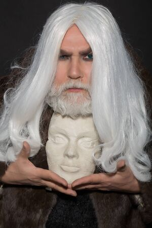 druid: old druid bearded man with long beard on serious face and hair in fur coat holding white sculpture head in hands with ring on dark background