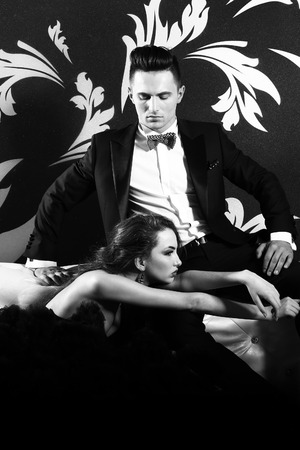 bed skirt: young handsome man in black suit and bow with pretty sexy woman in elegant evening dress with skirt and long curly hair on bed in bedroom Stock Photo