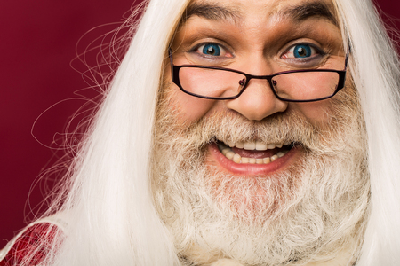 white beard: old bearded professor man wizard in glasses with blue lenses in eyes with long gray beard and white hair has emotional smiling happy face on purple background, portrait