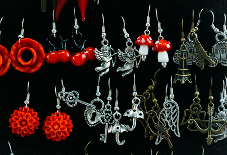 bazar: many small fashion female earrings red and silver colors on black fabric background sales in bazar