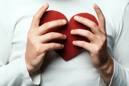 lad: male hands of man in white shirt holding red paper heart closeup