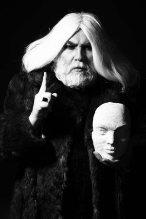 druid: old druid bearded man with long beard on serious face and hair in fur coat holding sculpture head in hands with ring on dark background, black and white Stock Photo