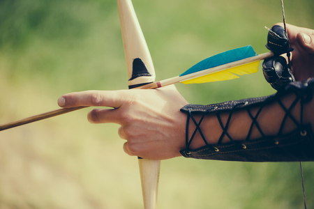 bowman: Archer hands with bow shoot arrow with blue and yellow fletchings on natural background