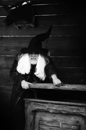 opens: Brutal druid old man with long silver hair and beard in Halloween hat opens vintage wooden chest black and white on log house background Stock Photo