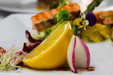 main course: Yellow lemon with onion sprouts salad fresh citrus fruit and vegetable garnish for main course on white background Stock Photo