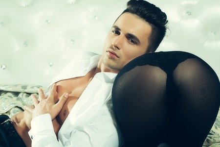 sixpack: handsome young man with sexy muscular body and bare chest with torso in open white shirt near female buttocks in black stockings
