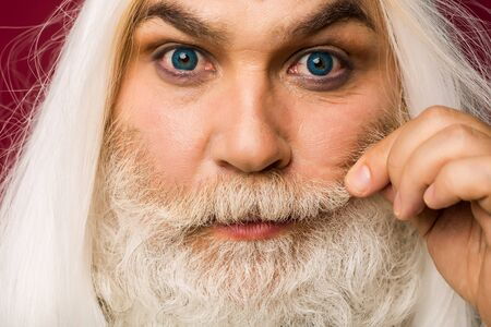 hait: old bearded man with long beard and white hait has eyes with bright blue lens, closeup