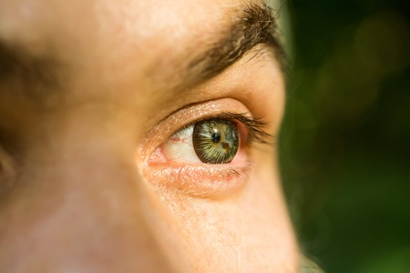 male eye with bright striped lens and hairy eyebrow of old man with wrinkled skin, closeup Stock Photo