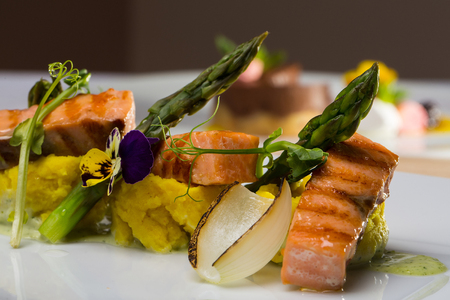 garnished: Grilled salmon steaks garnished with puree sauce flower asparagus and vegetables on white background