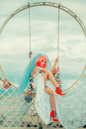 stylish hair: young woman with orange or pink hair and bright makeup on pretty face in white wedding dress red shoes and blue bride veil on natural cloudy sky background near floral swing