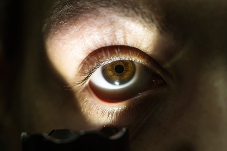 hairy closeup: young male with hairy eyebrow on serious face lighting on eye with flashlight in studio, closeup Stock Photo