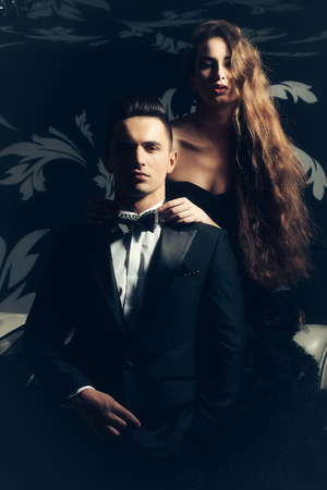 dress suit: young couple of handsome man in black suit and bow with pretty sexy woman in elegant evening dress with skirt and long curly hair